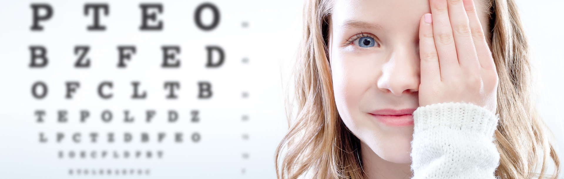 Young girl covering her left eye with an eye chart in the background