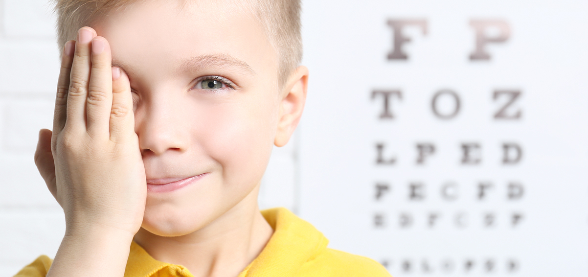 young boy covering one eye with an eye chart in the distance