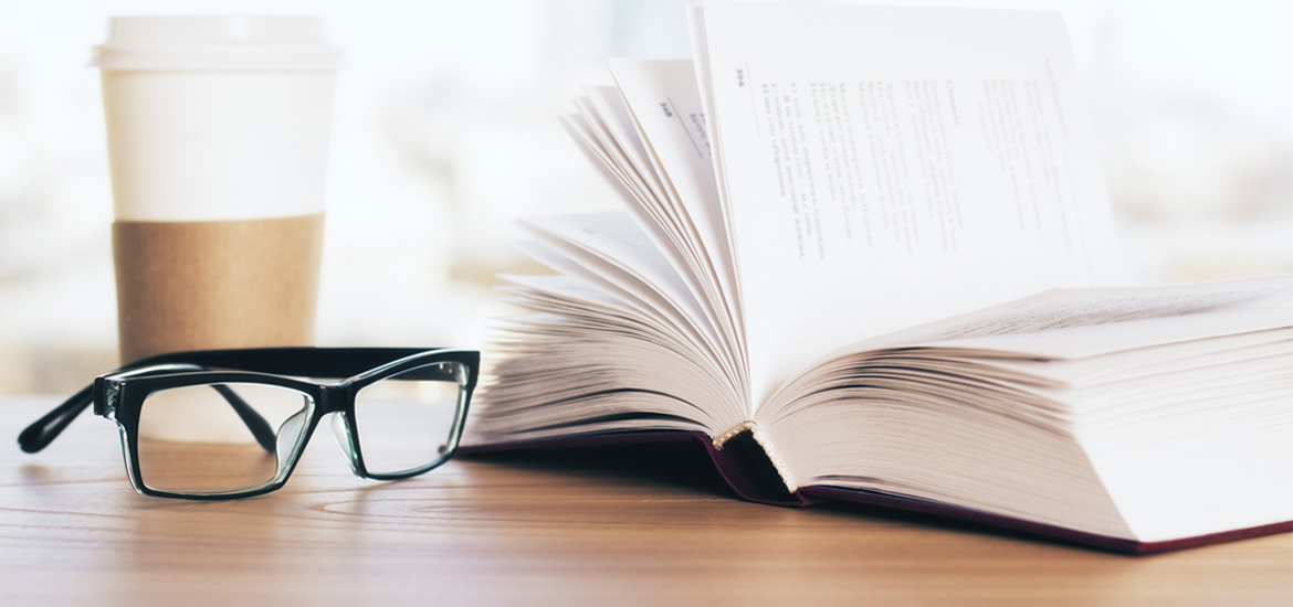 Glasses sitting beside an open book